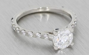 A Classic Round Brilliant Diamond Ring Accentuated With Elegant Diamond Shoulders.