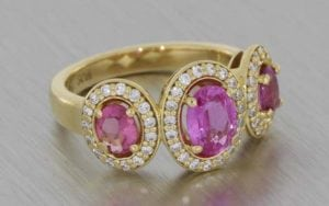 Striking Yellow Gold Trilogy Ring With Three Oval Pink Sapphires Surrounded By Diamond Halos