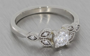 Platinum round diamond ring with diamond shoulder elements