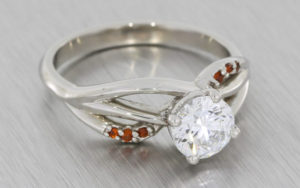 Organic platinum engagement ring set with a Brilliant cut Diamond and red garnets