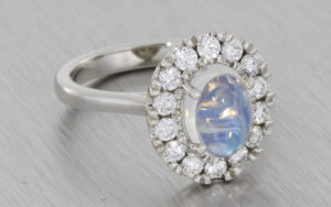 Platinum halo ring set with a moonstone and round brilliant diamonds