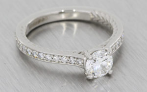 Platinum round brilliant diamond ring with intricate rope work and diamond set shoulders