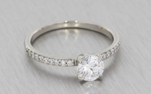 Round brilliant diamond ring housed in a 4 claw setting with grain set diamond shoulders