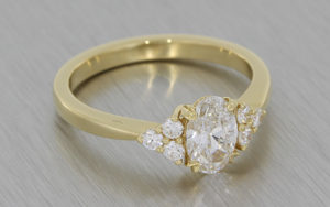 Yellow gold engagement ring featuring an oval centre diamond accented with small round diamonds