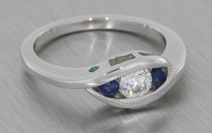 Bypass style white gold trilogy ring set with a a round brilliant diamond with two round sapphires either side