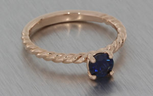 Rose gold twisted band with a round sapphire