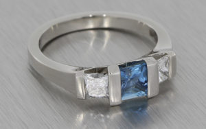 Modern engagement ring featuring square cut sapphire and diamonds